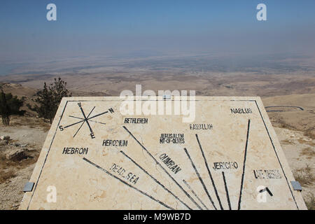 View from Mount Nebo over the surrounding countryside with an orientation table indicating key locations in Israel and Palestine. - Stock Photo