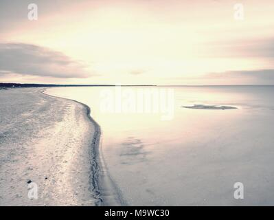 Island coastline within misty morning. Landscape with sandy beach and sea level ending in clouds. Warm Toned image - Stock Photo
