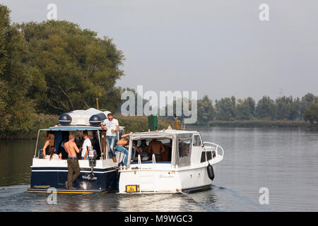 Group of young girls and boys having a party at two yachts at tnational park 'de Biesbosch' in the Netherlands - Stock Photo