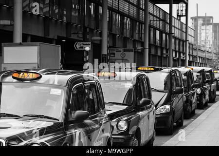 A queue of London black cab taxis in a row at a taxi rank, waiting to pick up passengers near Kings Cross station with for hire light illuminated - Stock Photo