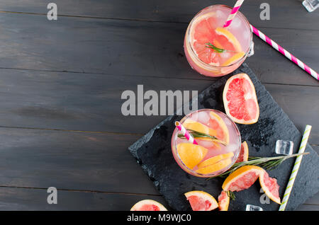 Cocktail with grapefruit slices and ice, ingredients for a drink on dark wooden table, copy space - Stock Photo