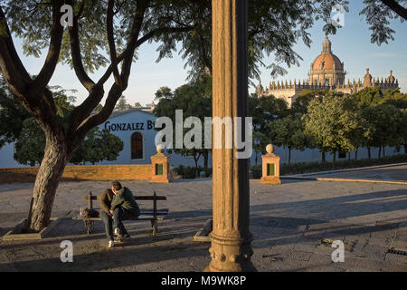 Couple kissing in Alameda Vieja park, in background wineries Gonzalez Byass and Cathedral. Jerez de la Frontera. Spain - Stock Photo