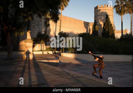 Man skateboarding, in Alameda Vieja Park, in background Alcazar, Jerez de la Frontera, Spain - Stock Photo