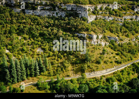 A road cuts through the limestone landscape of the Lot region in south west France. - Stock Photo