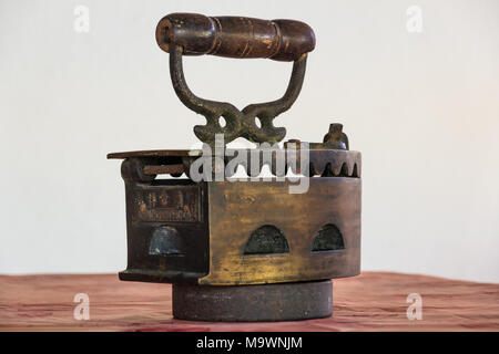 The back of an antique charcoal box iron with its own stand. - Stock Photo