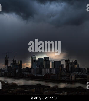 London, UK. 28th March, 2018. UK Weather: The last light breaks through a dark and dramatic evening sky just before the sun sets completely after a brief rain storm over east London including Canary Wharf business park buildings. Credit: Guy Corbishley/Alamy Live News - Stock Photo