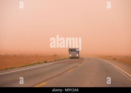 Big rig American bonnet car hauler semi truck with turn on headlight running on the road with very poor visibility in the red sand dust during huge sa - Stock Photo