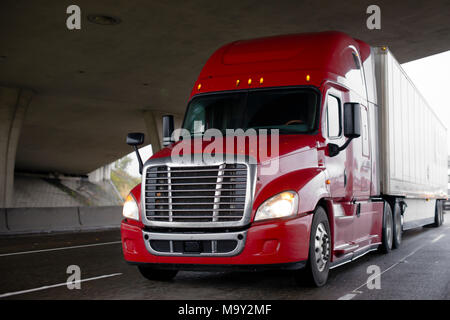 Bright red big rig modern semi truck fleet with shiny chrome grille and dry van trailer driving on highway under bridge across the road for timely del - Stock Photo