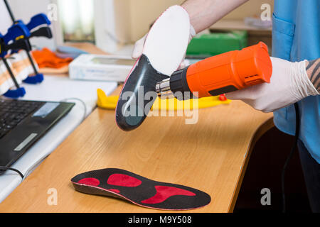 closeup Hands of young man with tattoo in workshop dressed in blue uniform make individual orthopedic insoles. The instrument uses hairdryer to heat and deform. Theme of small business and medicine - Stock Photo