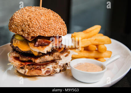 Close up of a delicious burger with sauce and fries - Stock Photo