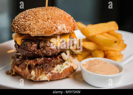 Close up of a tasty burger with sauce and fries - Stock Photo