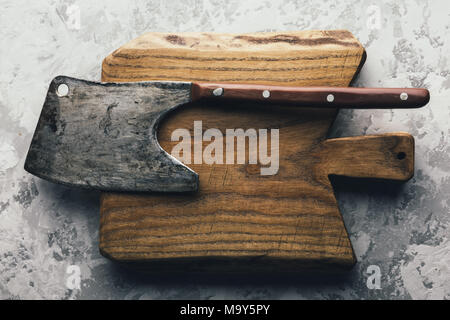Old rustic axe for meat on a wooden board - Stock Photo