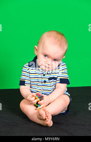 Sad 10 Month old Baby Boy on Green Screen playing with toy - Stock Photo