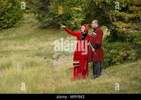 A man and woman wearing Georgian national dress stand on a rocky hillside, Upper Svaneti, Georgia - Stock Photo