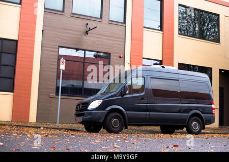 Black commercial mobile compact agile cargo minivan for small business and local delivery stand on the urban city street at industrial zone in front o - Stock Photo