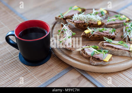Wholegrain sandwiches with micro greens and morning coffee cup. Vegan party food table with organic vegetables canapes. Healthy lifestyle, modern cooking ingredients and eating right concept. - Stock Photo