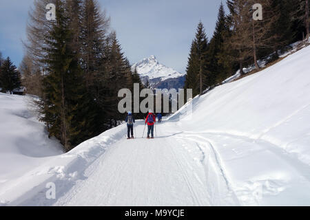 Two Women Walking on Snow Shoes on a Path in Fields above Badia, Italian Dolomites, Italy, EU. - Stock Photo