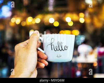 Hello text hand writing on cup with hand holding - Stock Photo