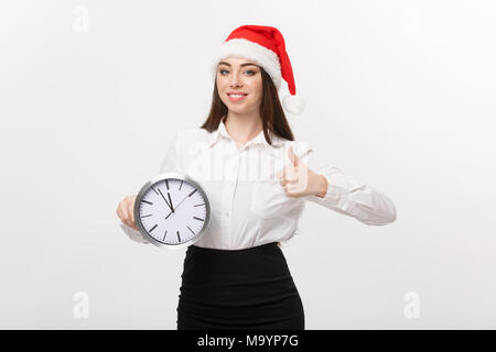 Time management concept - Young business woman with santa hat holding a clock and showing thump up isolated over white background. - Stock Photo
