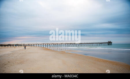 Man with dog walking on beach at sunrise with the Atlantic Beach pier in the background with sand, ocean, waves and blue clouds - Stock Photo