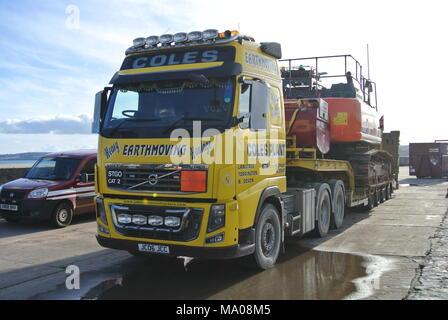 Volvo FH16 with low loader trailer and excavator on Haldon Pier, Torquay, Devon, England, UK - Stock Photo
