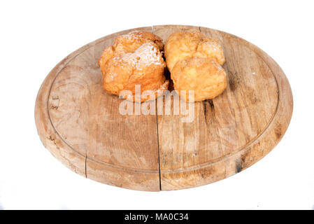 Fresh cream puffs on display on a wooden plate - Stock Photo