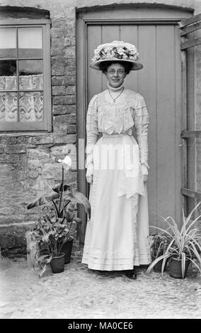 Young woman dressed as a bridesmaid in late Victorian England. She is wearing round spectacles, and is dressed entirely in white, with an elaborate white flowered hat. - Stock Photo