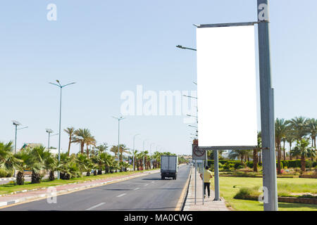 Blank mock up of vertical street poster billboard on summmer city background. - Stock Photo
