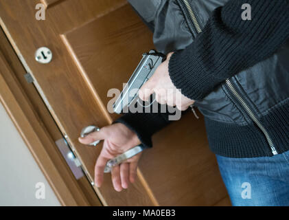 Armed man with gun waiting his victim near the door. - Stock Photo