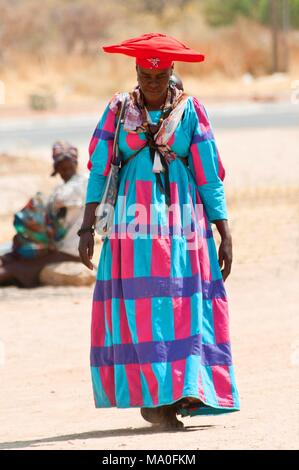 Herero woman in traditional dress and horned hat, Kaokoland wilderness region, Namibia, Africa. - Stock Photo