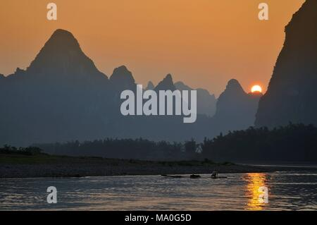 Scenic sunset over Karst mountains formations in Guilin, one of China most popular tourist destinations. - Stock Photo