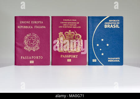 British, Italian and Brazilian passports standing next to each other. - Stock Photo