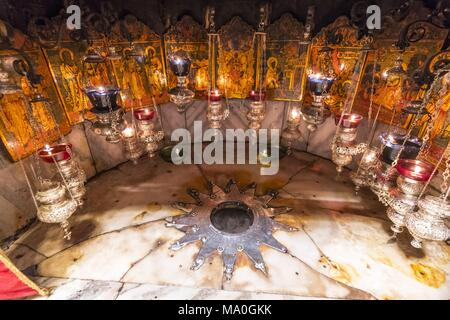 A silver star marks the traditional site of the birth of Jesus in a grotto underneath Bethlehem's Church of the Nativity, Palestine. - Stock Photo