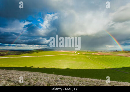 Early spring showers and rainbow over South Downs National Park in West Sussex, England. - Stock Photo