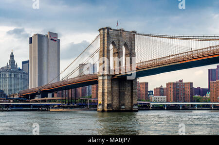 View of the Brooklyn bridge and the Manhattan skyline, in New York City. Photo taken from the ferry, while cruising East river. - Stock Photo