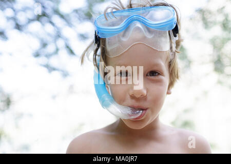 Portrait of a cute smiling young boy wearing a snorkel and mask on his head during the summer - Stock Photo