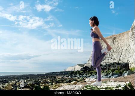 sportswoman doing a quad leg stretch by the sea - Stock Photo