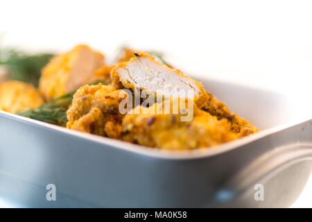 chicken fried in batter with dill in ceramic form on a white background - Stock Photo