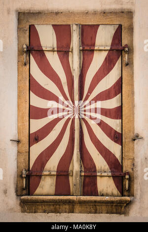 Detailed view of painted window shutter in red and cream colors with yellow casing - Stock Photo