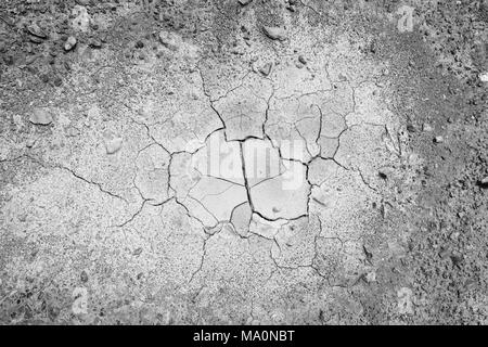 Stones and dry and cracked soil ground during drought, viewed from above in black and white with vignette. - Stock Photo