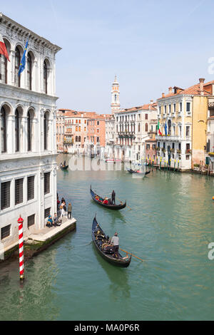Elevated view of gondolas on the Grand Canal, San Polo, Venice, Veneto, Italy taking groups of tourists on a sightseeing tour - Stock Photo