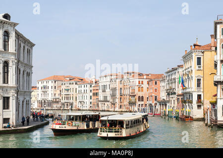 Two Actv vaporetto waterbuses (water buses) passing in the Grand Canal, Cannaregio, Venice,  Veneto, Italy filled with tourists using the public trans - Stock Photo