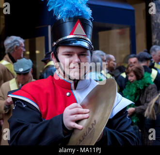 Boy holding symbols, at St. Patrick's Day Parade in New York, 2018. Marching band uniform, hat with blue feathers. Close-up, square. Gibson County Mar - Stock Photo