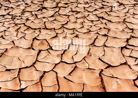 earth cracked by dryness in the desert, works as background or texture - Stock Photo