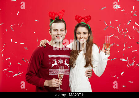 Christmas Concept - Happy caucasian man and woman in reindeer hats celebrating christmas toasting with champagne flutes, congratulating on xmas - Stock Photo