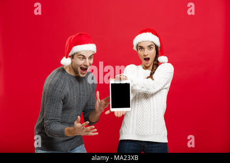 Christmas concept - Happy young couple in christmas sweaters surprising something in digital tablet - Stock Photo