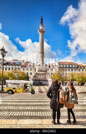 5 March 2018: Lisbon, Portugal - two young women wait to cross the road into Rossio Square. In the centre is the Column of Pedro IV. - Stock Photo
