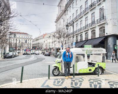 7 March 2018: Lisbon, Portugal - Tuk tuk driver wrappede up warm,  waiting for business on the streets of Lisbon in early spring. - Stock Photo