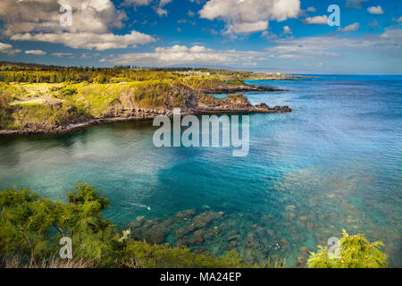 Snorkelers in Honolua Bay, Maui, Hawaii.  The Ritz Carlton Hotel can be seen behind the two points of land and the island of Lanai is in the backgroun - Stock Photo