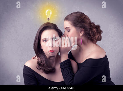 A young girl has an idea illustrated with a drawn glowing light bulb above the head, while a friend whispers a secret in her ear concept. - Stock Photo